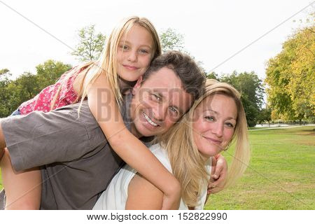 Mom And Dad Giving Piggyback Ride To The Daughter