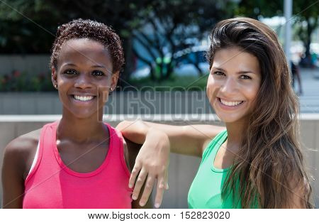 Caucasian hipster girl with african american woman outdoor in the city in the summer