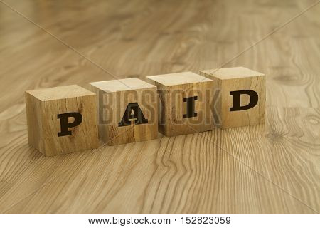 Paid word written on wooden blocks on wooden background.