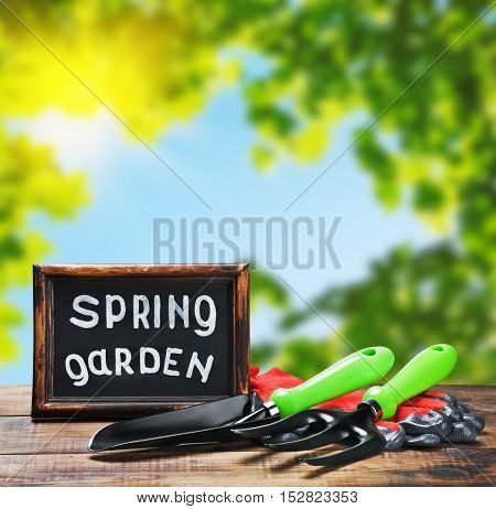 garden tools lying on a wooden table on a background of spring garden