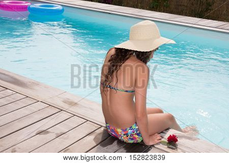 Woman In Bikini And Summer Hat Relaxing By The Swimming Pool