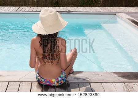 Girl In Bikini Meditating By The Swimming Pool