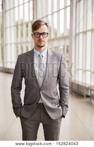 business, corporate and people concept - young businessman in suit and glasses at office