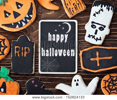 Handmade Halloween cookies on a wooden background and a blackboard