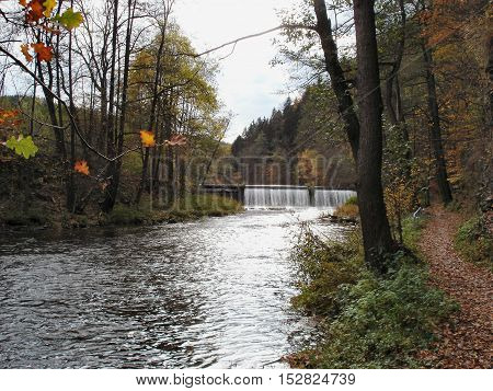 Weir at the Zschopau River in Saxony, Germany; landscape in the fall; colorful trees and hiking path at the river