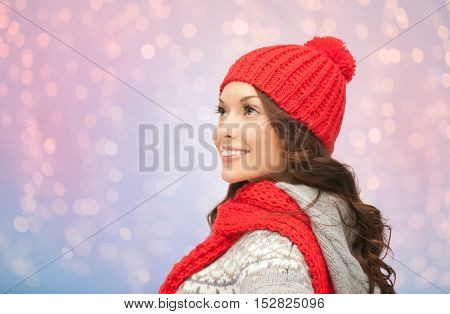 winter holidays, christmas and people concept - smiling young woman in red hat and scarf over rose quartz and serenity lights background