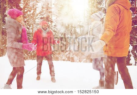 christmas, season, friendship and people concept - group of happy men and women having fun and playing with snow in winter forest