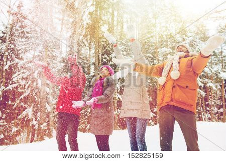 love, relationship, season, friendship and people concept - group of smiling men and women having fun and playing with snow in winter forest