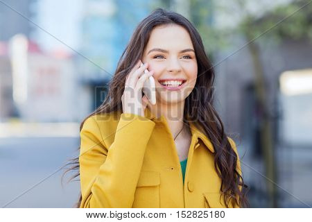 technology, communication and people concept - smiling young woman or girl calling on smartphone on city street