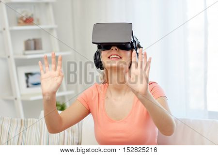 technology, virtual reality, entertainment and people concept - happy young woman in virtual reality headset or 3d glasses and headphones playing game at home and touching something invisible