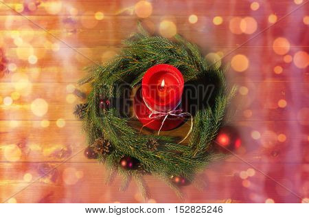 christmas, decoration, holidays and advertisement concept - close up of natural green fir branch wreath with red burning candle over lights