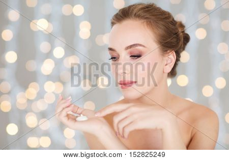 beauty, people, skincare and cosmetics concept - happy young woman with moisturizing cream on hand, over holidays lights background
