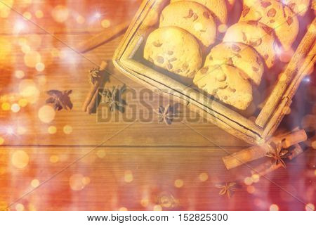 baking, christmas, holidays and food concept - close up of oat cookies in wooden box, and cinnamon on table over lights