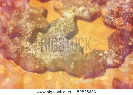 baking, cooking, christmas, holidays and food concept - close up of gingerbread dough on wooden board over lights