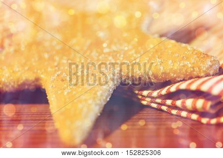baking, cooking, christmas, holidays and food concept - close up of gingerbread cookie and towel over lights