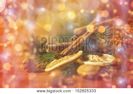 decoration, winter, holidays and new year concept - close up of christmas fir branch with cinnamon and dried orange on wooden table over lights
