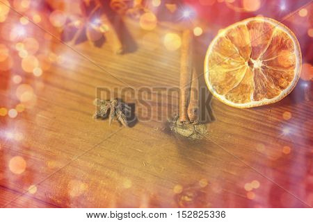 christmas, holidays, cooking and spice concept - close up of cinnamon, anise and dried orange on wooden board over lights