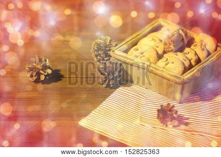 christmas, baking, culinary, holidays and food concept - close up of oat cookies in wooden box with cinnamon and pinecones on table over lights