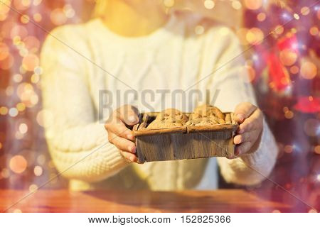 christmas, holidays, baking, people and food concept - close up of woman with oat cookies sitting at wooden table over lights