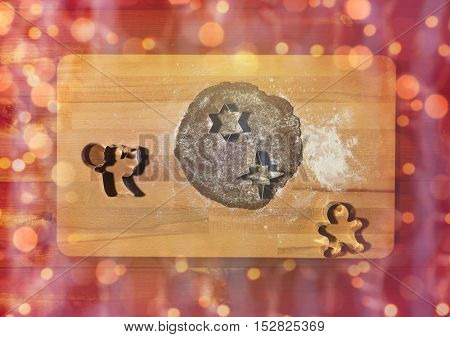 baking, cooking, christmas and holidays concept - close up of gingerbread dough, molds and flour on wooden cutting board from top over lights