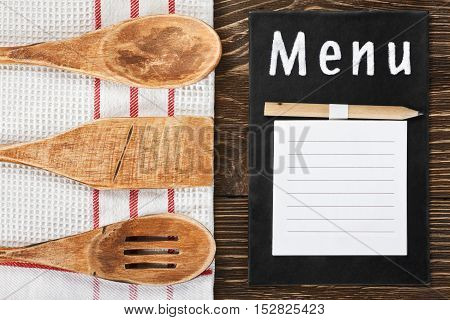 Wooden kitchen utensils and a notepad to write the menu