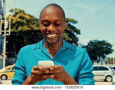 African american man surfing the internet by phone outdoor in the city in a warm cinema look