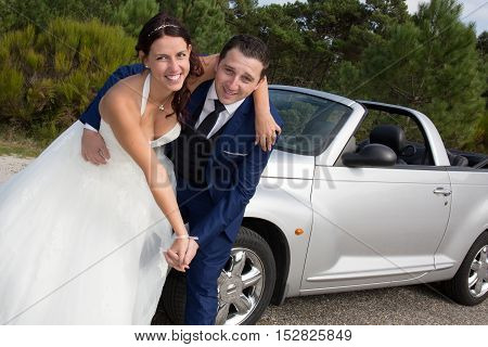 Lovely Newly Wed Couple In Front Of Grey Cabriolet
