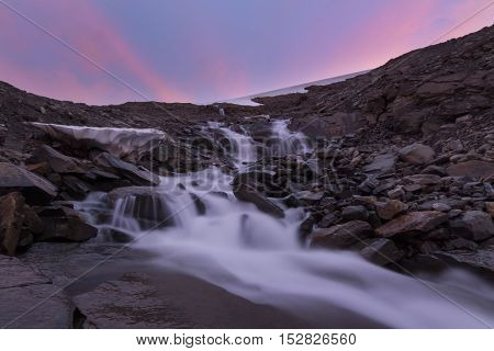 River of melt water from glacier and pink sunset background