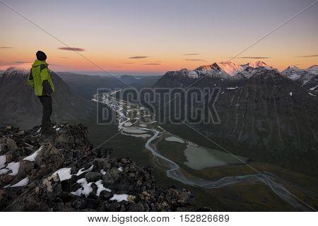 Hiker enjoying the view of a river shapen valley, Rapadalen, Sweden