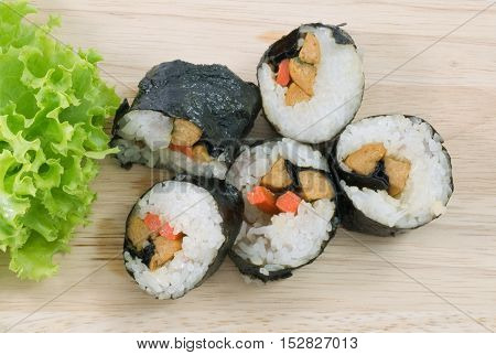 Japanese Cuisine Top View of Fresh Veggie Sushi Rolls or Vegetable Maki with Green Oak on Wooden Tray.