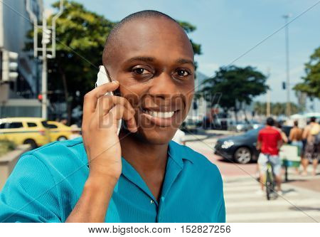 Happy african man using cellular in the city in a warm cinema look