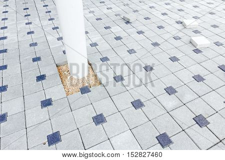 White steel pillar is carrier of construction; ground is covered with new colored brick pavement.