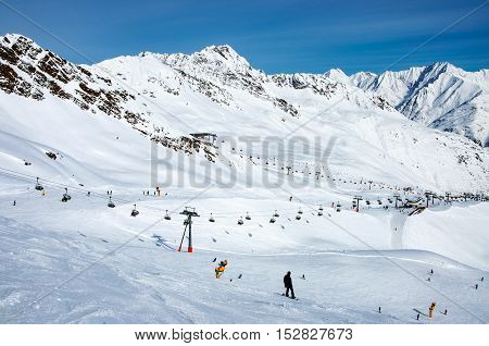 Ski lifts, skiers, snowboarders, pistes and winter sports infrastructure on the slopes of Giggijoch mountain in Solden resort in Otztal Alps in Austria