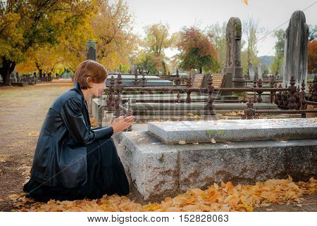 Young woman dressed in black praying at grave in cemetery, with falls leaves in the background