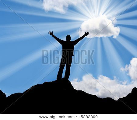 Silhouette of a man with his arms stretched out to the sun.