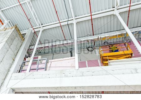 Cherry picker is parked upward at indoor construction site of unfinished modern large showroom.
