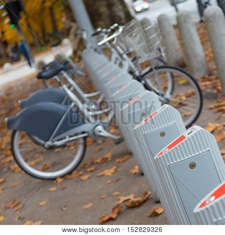 Station of urban bicycles for rent downtown. Green sustainable ecological public transport. Healthy lifestyle.