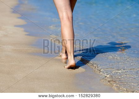 Legs of woman walking on the sand of the beach