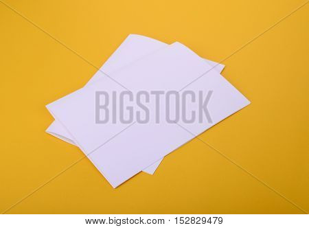 two white paper bifold brochure mockup on yellow background