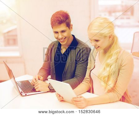 school, education, technology and internet concept - two teens with laptop and tablet pc at school