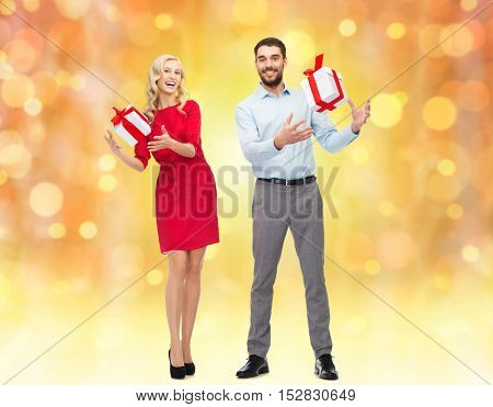 people, christmas, birthday, couple and holidays concept - happy young man and woman with gift boxes over lights background