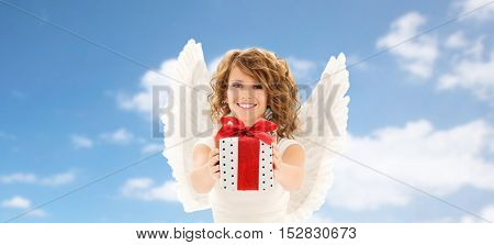 people, holidays, christmas, birthday and religious concept - happy young woman with angel wings holding gift box over blue sky and clouds background