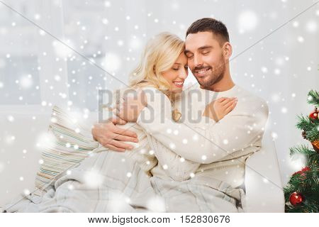 family, love, winter holidays, christmas and people concept - happy couple hugging on sofa at home
