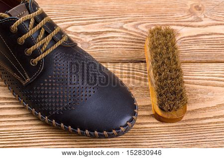 Men's leather shoes and shoe brush on the wooden background