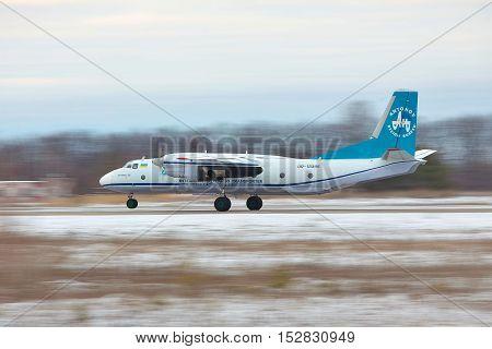 Kiev Region Ukraine - January 31 2011: Antononv An-26 cargo plane is taking off from the runway in snow storm