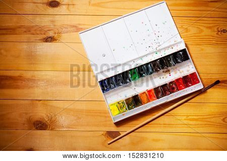 Watercolor aquarell paints in box with brush on wooden background