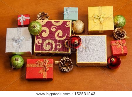 Gift boxes and christmas balls on wooden background. Selective focus