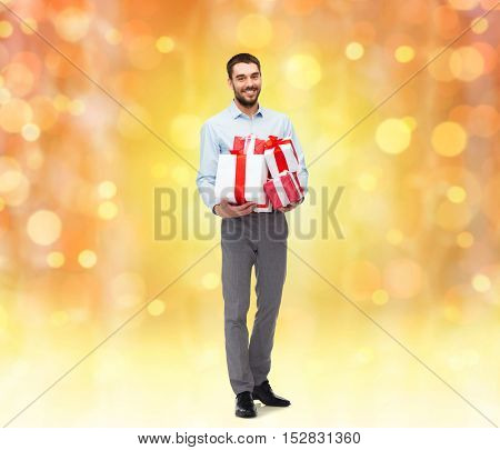 people, christmas, birthday and holidays concept - happy young man holding gift boxes over lights background