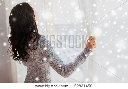 people, winter, christmas and home concept - close up of happy woman opening window curtains over snow