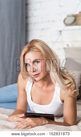 Enjoying free time. Beautiful blond-haired lady lying on bed, holding slim tablet and looking forward.